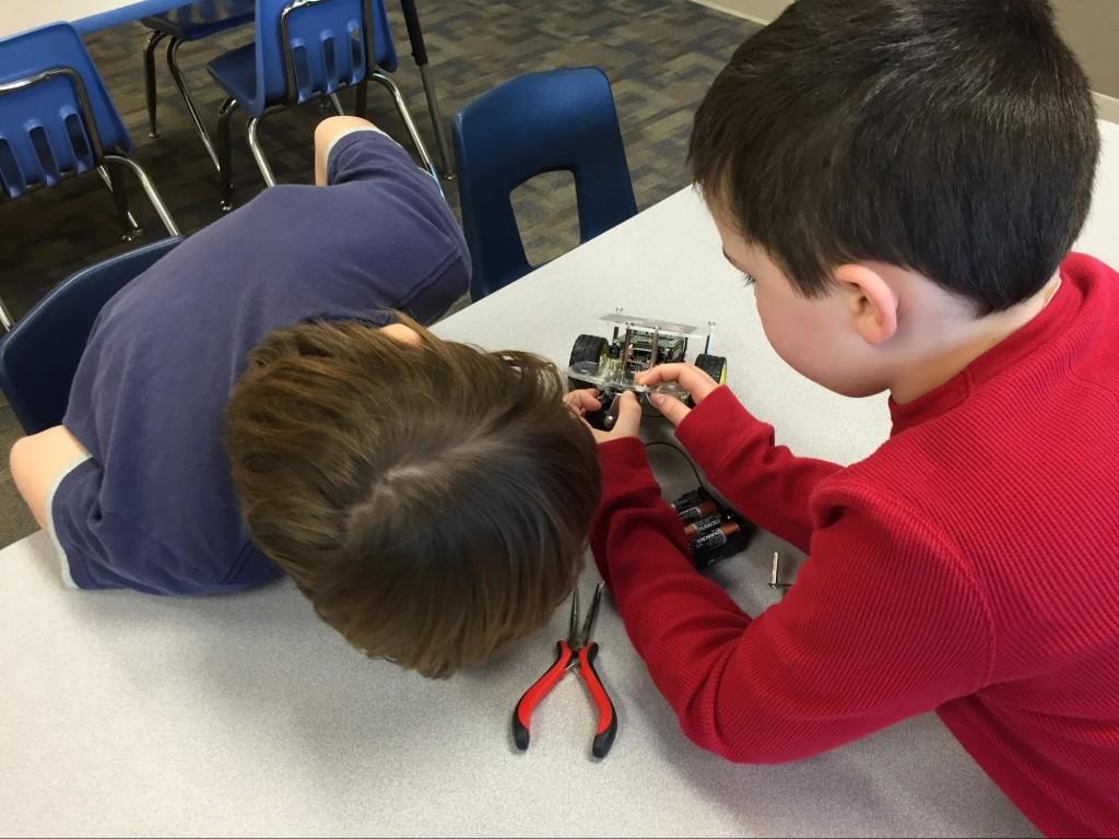 Landon and Brady installing the new caster on the GoPiGo.
