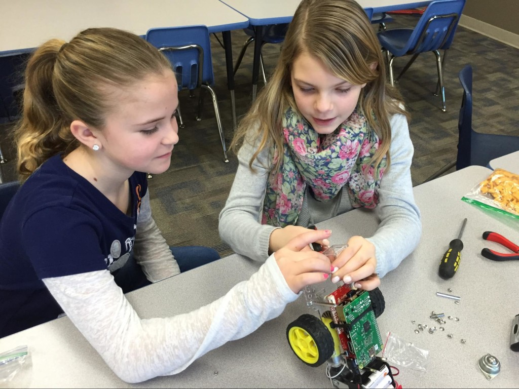 Madison and Kelsey hacking a sensor mount to work with a Raspberry Pi camera.